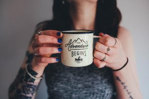 Woman holding metal cup with The Adventure Begins logo