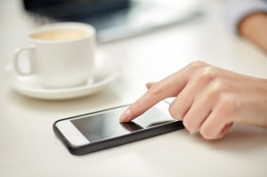 close up of woman hand with smartphone and coffee