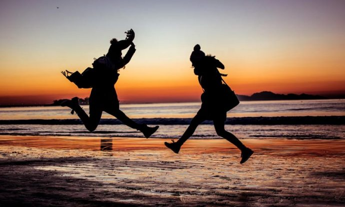 silhouetted people jumping on beach at sunset